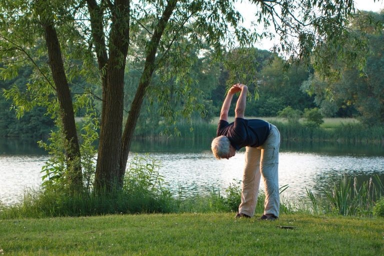 man bending over next to river